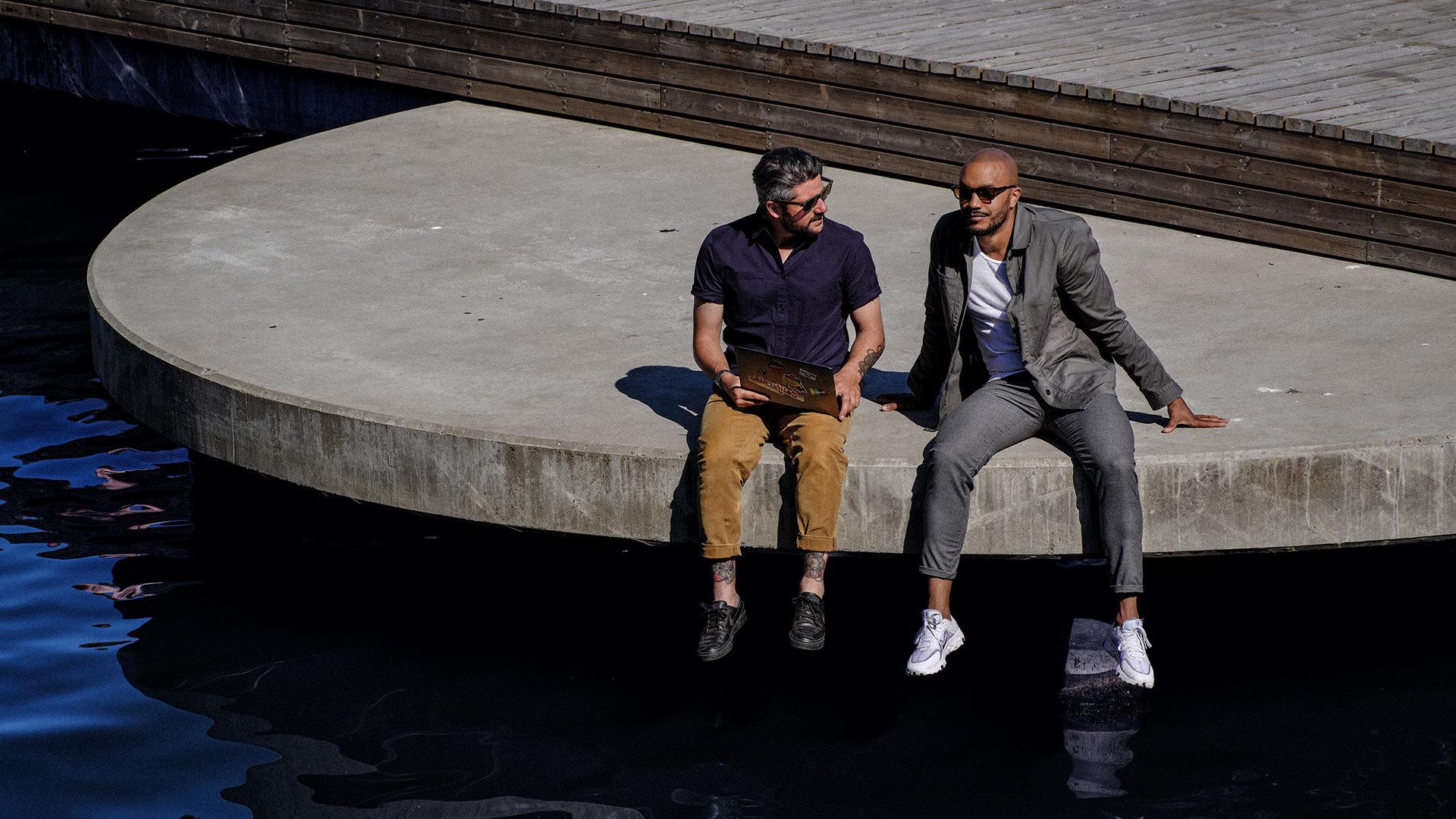 Ett par sitter vid vattnet